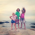 Three kids on a rock at the beach