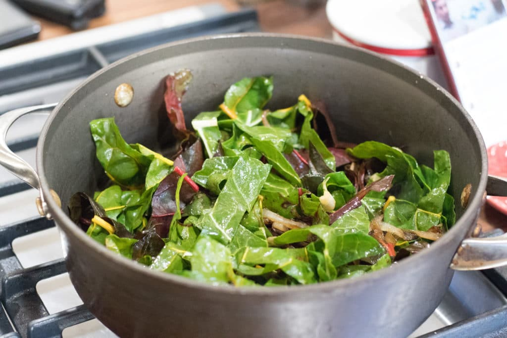 swiss chard and sauteed onions in a pan