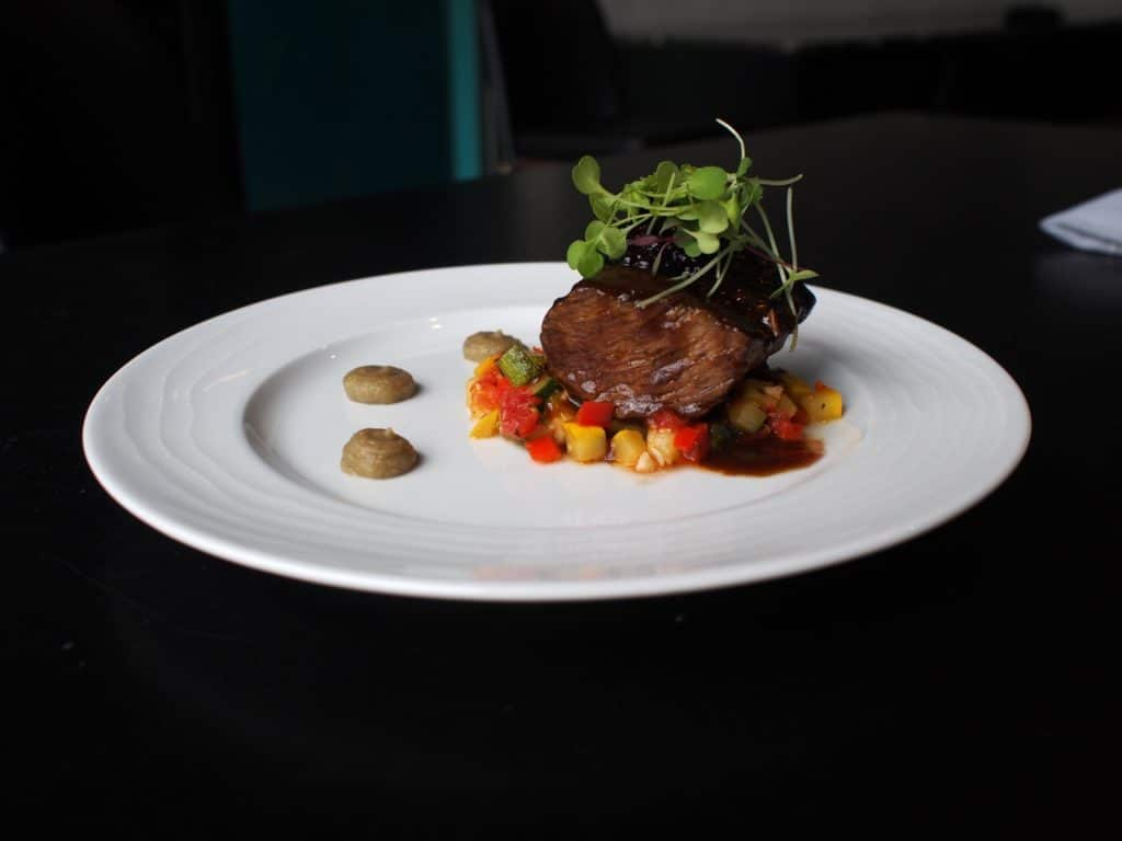 Carolina Bison Shoulder Braised in Green Man Porter served over a ratatouille of summer sqashes, with roasted Garlic eggplant puree and Appalachian Blackberries