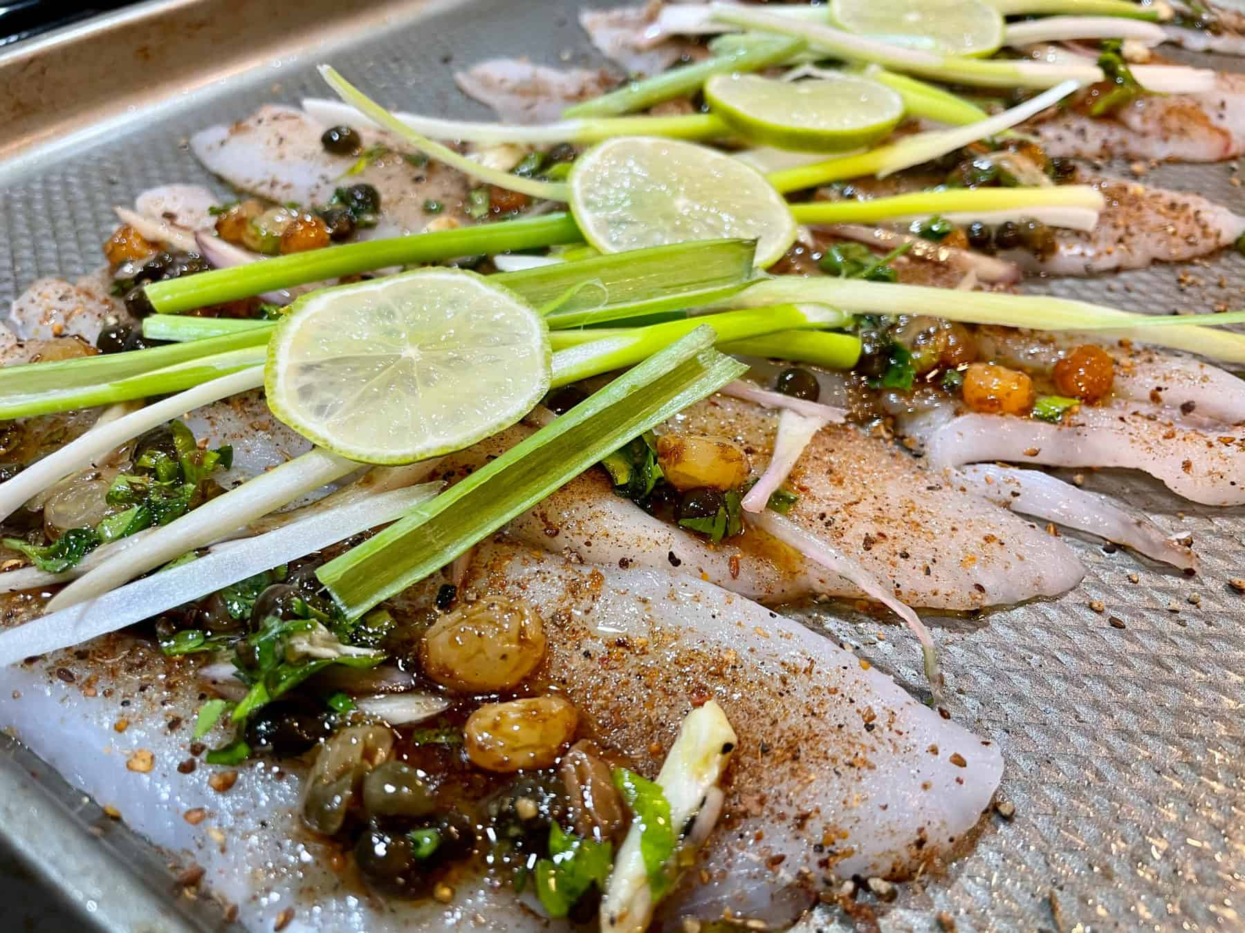 Solel and limes and scallions on a pan